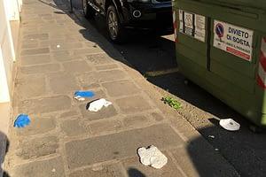 Mascherine e guanti buttati vicino ai cassonetti dei rifiuti